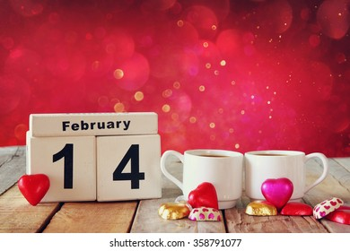 February 14th wooden vintage calendar with colorful heart shape chocolates next to couple cups on wooden table. selective focus. vintage filtered