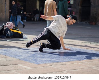 February, 16 2019 Bologna, Italy. Some boys dance break dance in the middle of a street in Bologna, Italy and in front of a church.