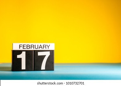 February 17th. Day 17 of february month, calendar on yellow background. Winter time. Empty space for text