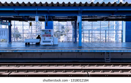 February 19, 2019 - Miyazaki, Japan :: A man sit on a chair in blue railway staion with a view of Miyazaki street