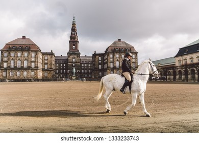 February 20, 2019. Denmark. Copenhagen. Training bypass Adaptation of a horse in the royal stable of the castle Christiansborg Slots. Man rider in uniform and helmet and racehorse outdoors.