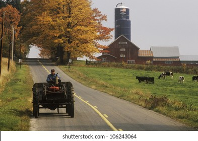 FEBRUARY 2005 - Tractor on farm road with barn and silo in background in autumn, VT