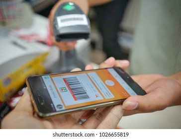 February, 2018 : man scanning barcode on app seven eleven mobile ( true wallet ) at seven eleven shop at Bangkok,Thailand