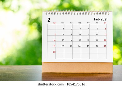February 2021 Calendar desk for organizer to plan and reminder on wooden table on nature background.