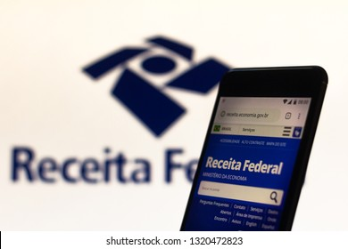 """February 22, 2019, Brazil. Homepage of the Brazilian """"Receita Federal"""" displayed on the screen of the mobile device. Soon it appears in the background. Concept of income tax."""