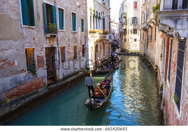 February 25, 2017. Venice street with gondolas; Boats and houses.