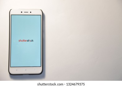 February 26, 2019. Kiev, Ukraine. shutterstock The program is a smartphone on a white background. Work on the smartphone using your hands