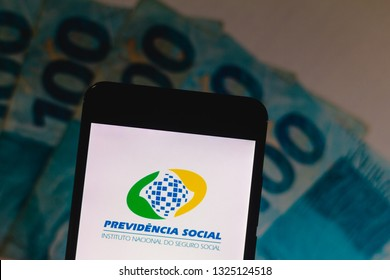 February 27, 2019, Brazil. Social Security Logo (INSS) displayed on the screen of the mobile device. Money notes in the background. Concept of retirement, pension and rights.