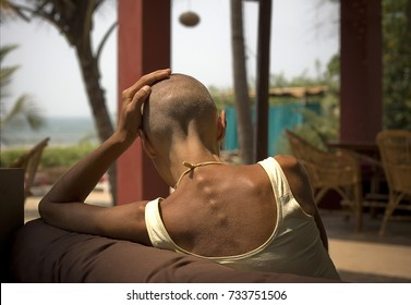 February 28, 2010 - Mandrem, Goa, India. The bald yoga woman, sitting from the back, in front of Arabian sea.