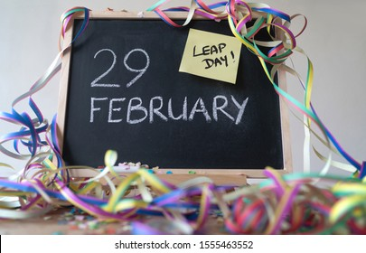 February 29 written on chalk board, with yellow post-it with text Leap Day.  Board is surrounded with festive confetti and ribbons. Placed on a wooden underground and white background.