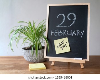 February 29 written on chalk board in vertical position, with yellow post-it with text Leap Day. Accompanied by light green plant and post-it block.  Placed on wooden underground and white background.