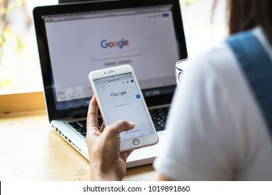 February 4, 2017: Women are typing on Google search engines from iphone and laptop phones. Google search with the new Google logo is a great internet search engine. And the most popular in the world.