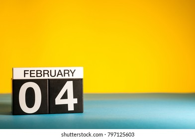 February 4th. Day 4 of february month, calendar on yellow background. Winter time. Empty space for text