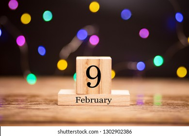 February 9th. Day 9 of february month set on wooden calendar at center of dark background with garland bokeh. Winter time. Empty space for text, mockup.