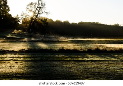 February dawn misty sunrise across a golf course