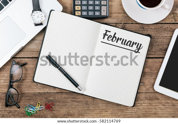 February text in note book on office desk with electronic devices, computer and paper, wood table from above, concept image for blog title or header image.