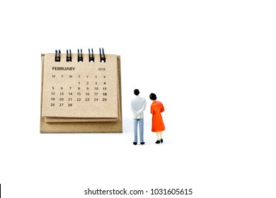 February. Two thousand eighteen year calendar and two miniature plastic figures. Man and woman on white background. Planning for the future â?? marriage, wedding or pregnancy.