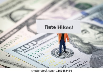 FED consider interest rate hike, world economics and inflation control, miniature man holding Rate Hikes sign standing on US Federal Reserve emblem on dollars banknote.