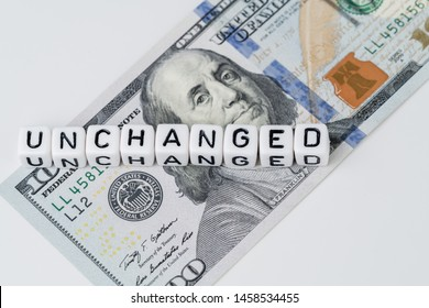 FED, Federal Reserve with interest rate remain unchanged concept, small cube block with alphabet building the word Unchanged next to Federal Reserve emblem on US Dollar banknote.