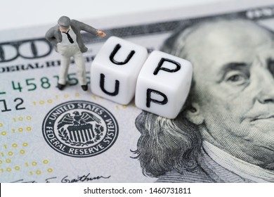 FED, Federal Reserve with interest rate cut concept, businessman standing with small cube block with alphabet building the word CUT next to Federal Reserve emblem on US Dollar banknote.