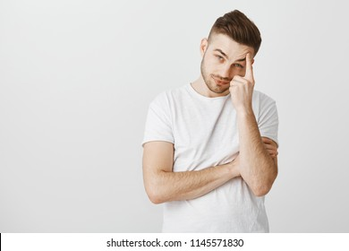 Fed up indifferent and bored handsome stylish male with beard and cool hairstyle tilting head leaning on finger raising eyebrows and gazing careless with boredom at camera over gray background