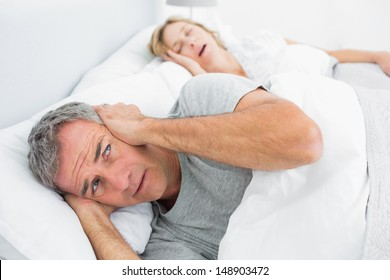 Fed up man blocking his ears from noise of wife snoring at home in bedroom
