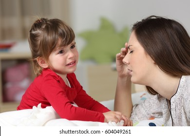 Fed up woman listening to her two years old daughter crying sitting on the bed in a house interior