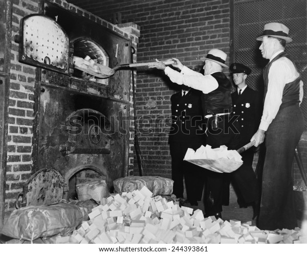 Federal Bureau of Narcotics agents shovel confiscated heroin blocks into incinerator in 1936.