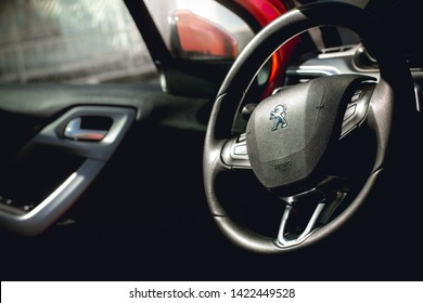 Brasília, Federal District - Brazil. June, 12, 2019. Photo of the interior of a car peugeot 208 griffe1.6 automatic model 2014. Highlight the vehicle steering wheel with a company logo.