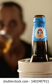 Brasília, Federal District - Brazil. May, 19, 2019. Antarctica Pilsen.  Photo of a bottle of Antarctica beer and a man drinking in the background. The Antarctica Brand is very famous in Brazil.