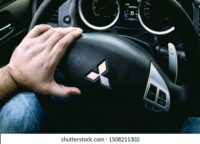 Brasília, Federal District - Brazil. September, 18, 2019. Photograph of a man holding a steering wheel of a car Mitsubishi Lancer Gt 2015.