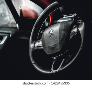 Brasília, Federal Distritc - Brazil. June, 12, 2019. photo of the interior of a car peugeot 208 griffe1.6 automatic model 2014. Highlight the vehicle steering wheel with a company logo.