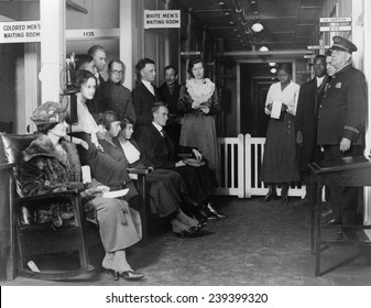 """Federal employees """"White Men's Waiting Room,"""" at the Public Health Service Dispensary, in Washington, D.C. Race discrimination sign, """"Colored Men's Waiting Room,"""" appears at left. Photo ca.1920."""