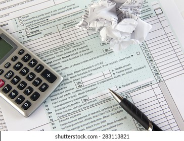 Federal income tax form 1040 with crumpled tax forms, pen and calculator. Concept for  frustration, difficulty and needing help in understanding tax laws and regulations