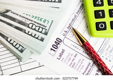 federal income tax return IRS 1040 documents with pen, calculator, dollars