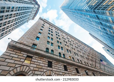 The Federal Reserve Bank of New York, upward view, and surrounding buildings.