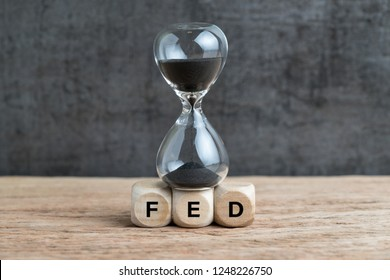Federal Reserve, FED target and speed to raise interest rate concept, hourglass or sandglass on cube wooden block with alphabet building acronym FED on wooden table with dark background.