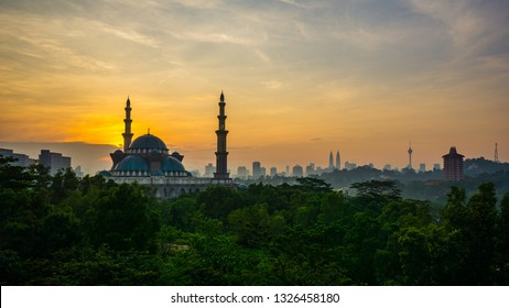 The Federal Territory Mosque during sunrise with Kuala Lumpur city skyline on the background.