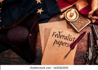 Federalist papers and the birth of the United States of America concept with tricorn hat, candle, feather quill, musket gun, the Betsy Ross American flag and aged paper