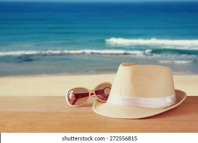 fedora hat and sunglasses over wooden table and sea landscape background. relaxation or vacation concept