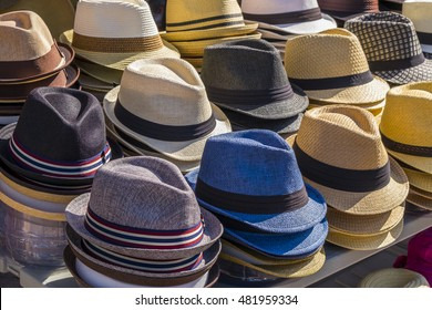 Fedora hats in various colors stacked on a table ready for sale.