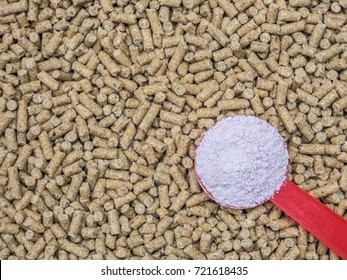 Feed additive in red spoon on blurred animal feed background, antibiotics in animal feed concept.