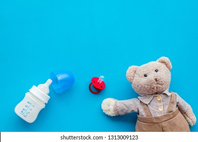 Feed baby concept. Teddy bear toy near small bottle with food on blue background top view copy space