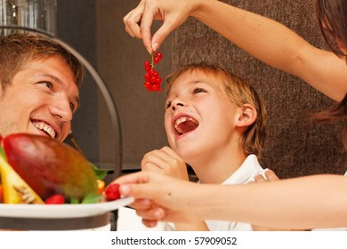 feed me - mother feeding son with berries