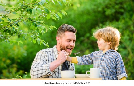 Feed son solids. Feed your baby. Natural nutrition concept. Dad and cute toddler boy having lunch outdoors. Child care. Feeding son natural foods. Feed in right way for childs stage of development.