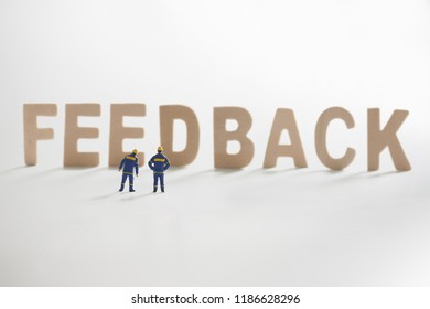 FEEDBACK word  with Miniature people: Engineer standing infront use as business concept.