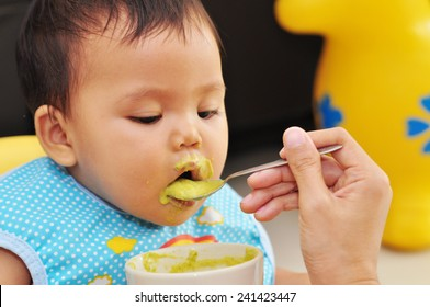 feeding baby food to baby