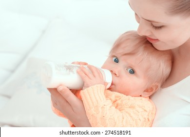Feeding of a baby. Mother watching and holding her baby eating from the bottle