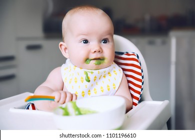 Feeding. Messy smiling baby eating with a spoon in high chair. Baby's first solid food. Mother feeding little child with spoon of puree. Daily routine. Finger food. Healthy child nutrition.