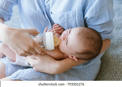 feeding the newborn with a mixture in a bottle. artificial nutrition. mother's love and warmth